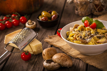 chicken and mushroom tagliatelle shot on wood boards at an angle with a copper pot loose mushrooms vine tomato parmesan block grater basil landscape