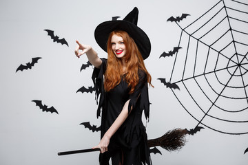 Halloween Concept - Happy elegant witch enjoy playing with broomstick.