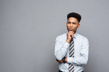 Business Concept - Confident professional african american businessman in thinking posture over grey background.