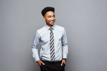 Business Concept - Happy confident professional african american businessman posing over grey background.