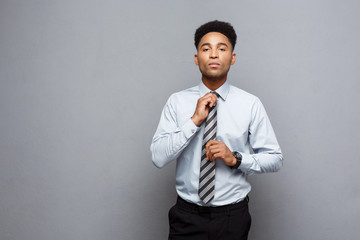 Business Concept - Confident professional african american businessman tie one's necktie over grey background.