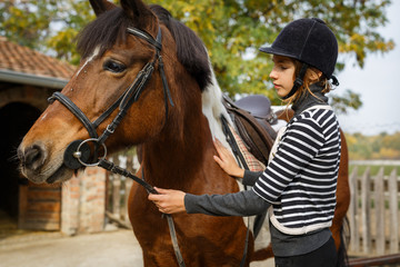 Preparing for training. Teenage girl with her horse in front of a stable