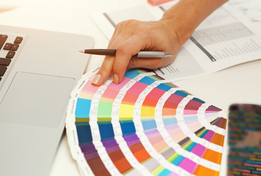 Hand with different color pattern samples on the office table
