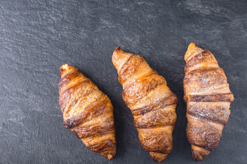 Three croissant sprinkled with powdered sugar on a gray background
