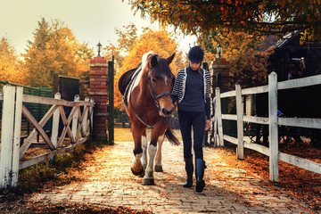 Teenage girl with her horse in front of a stable