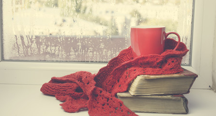 books with cup of coffee on window