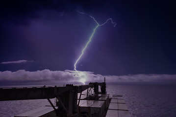 Thundertorm in sea with lightnings in sky and ship