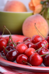 fresh sweet cherries in bowl on table close up. Apricot and orange