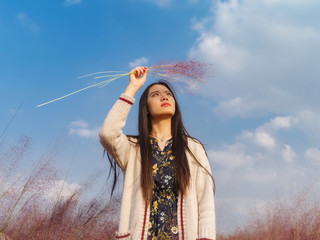 Portrait of beautiful young Chinese woman wearing white sweater standing in the pink hairawn muhly field, using pink grass to protect sun shine.