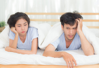Relationship difficulties, conflict and family concept - unhappy couple having problems at bed - lover with conflict and stress on bedroom.
