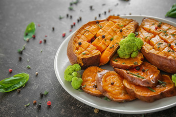 Plate with baked sweet potato on table