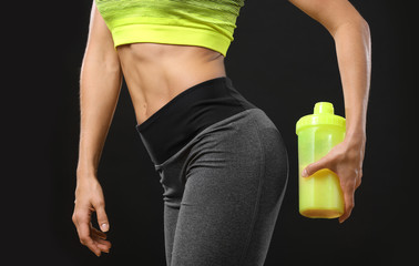 Young woman holding bottle with protein shake on black background