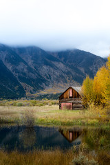 An old rusty abandoned wooden barn by the yellow aspen trees and its reflection on the small pond. Foggy mountain in autumn fall foliage season in the background.
