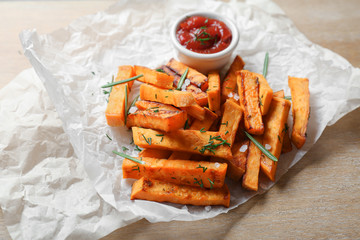 Parchment with sweet potato fries on table