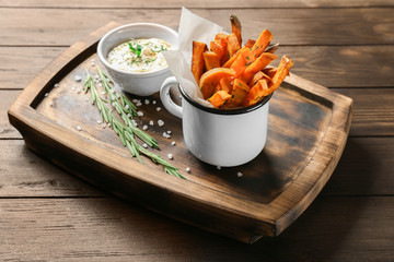 Board with sweet potato fries in mug on table