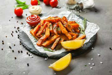 Slate plate with sweet potato fries on table