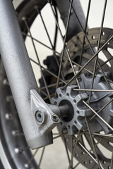 front wheel components of vintage European motorcycle; macro photograph of front bike wheel with spokes and brake parts