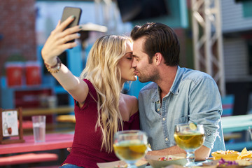 romantic couple taking selfie of themselves kissing while at mexican taco restaurant