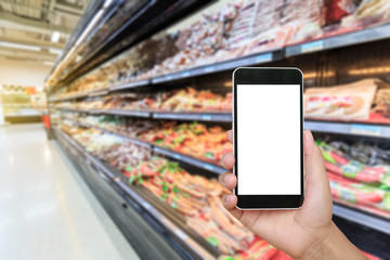 Hand holding smartphone with white blank screen and blurred supermarket ham sausage background