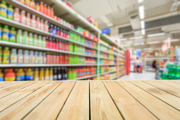 Empty wooden table and supermarket blurred drink background