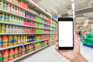 Hand holding smartphone with white blank screen and blurred supermarket drink background