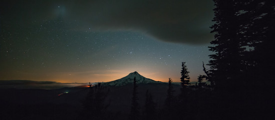 Silhouette of Mt. Hood at night with glow of Portland in distance