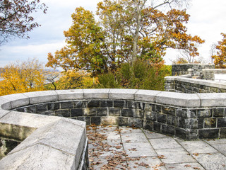 Looking at Autumn Leaves Over a Stone Wall at the Hudson River in Manhattan, New York