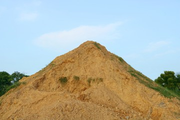 Piles of sand and stone on blue sky background.