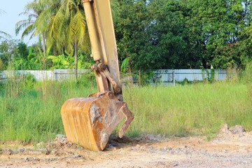 Heavy yellow excavator digging with floor soil.