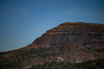 Desert mountain cliff at night with blue moonlit sky