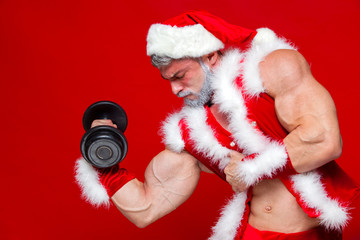 Holidays and celebrations, New year, Christmas, sports, bodybuilding, healthy lifestyle - Muscular handsome sexy Santa Claus.Isolated on red background.