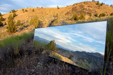 Mirror in the desert looks like a portal to the wilderness and blue skies and clouds