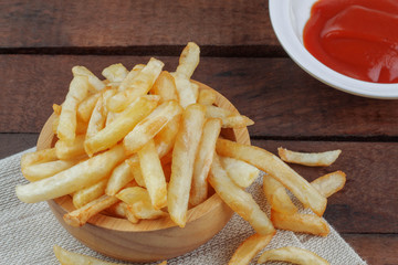 French fries and sauce on wooden.
