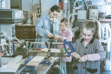 Schoolgirls learning to carve wood during arts and crafts class