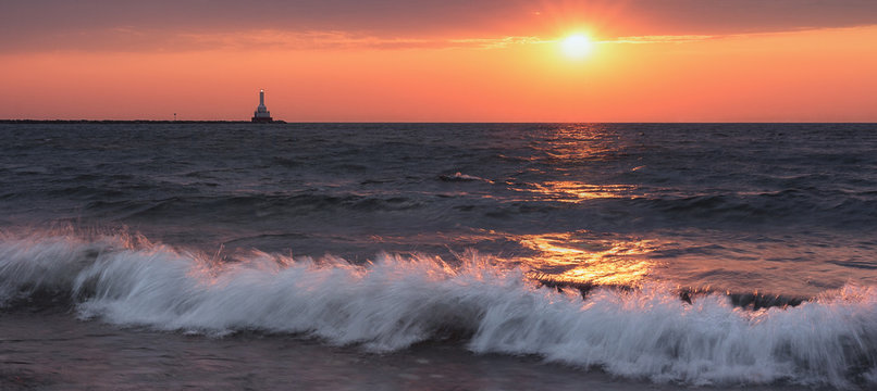 Sunset Waves Crashing. Wide Tranquil Beach under a Fiery Orange Sky. Lake Superior Seascape. Natural Beauty Background with Oceans of Copy Space.