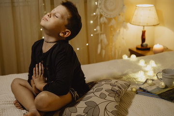 Cute boy praying for gift with eyes closed in the evening room on a bed on a background of lights
