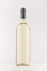 Transparent wine bottle with white wine on white wooden board, mock up, vertical. Template for advertising, design, branding identity.