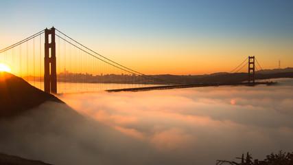 Spectacular Sunrise at Golden Gate Bridge with low fog.