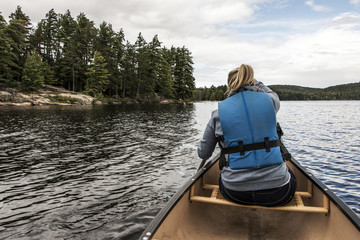Girl canoeing with Canoe on the lake of two rivers in the algonquin national park in Ontario Canada on sunny cloudy day