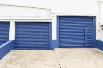 two blue storage gates for trucks with angled ramps -commercial building