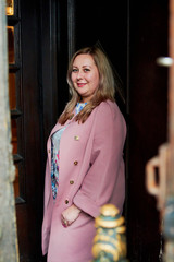 portrait of a beautiful plus size blonde girl in a pink coat near vintage door