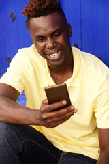 Cheerful young afro american man sitting outside and using mobile phone