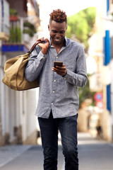 Young african american male traveler walking outside and using mobile phone