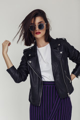 Wall Mural - Young beautiful woman in a black jacket and sunglasses