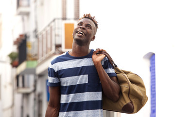 Smiling african male traveler outdoors on street with bag