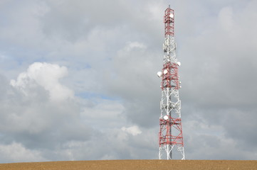 Telecommunication towers against cloudy sky
