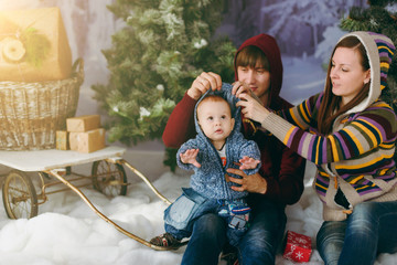 Young playful happy parents with a cute little baby boy in a decorated forest with fir trees, sledges and gift boxes. Christmas good mood. New Year. Lifestyle, family and togetherness concept.