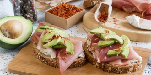fresh bread with cottage cheese, prosciutto , avocado and saffron
