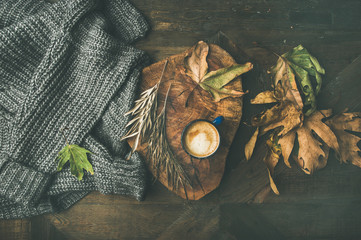 Autumn or Fall morning coffee concept. Flat-lay of knitted woolen grey sweater, wooden tray, mug of coffee and yellow fallen leaves over dark rustic wooden table background, top view