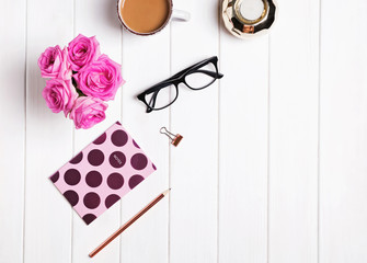 Stylish desk. Coffee, flowers, glasses and other accessories